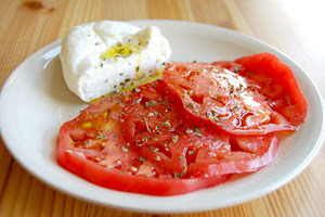 Beefsteak tomato with burrata, olive oil, and oregano.