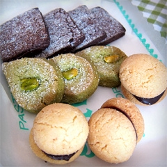 A small tray of paste da tè: chocolate and pistachio shortbreads, and'Baci di Dama' (Ladies' Kisses), a traditional Piedmontese cookie made of two crumbly hazelnut or almond halves held together with a layer of dark chocolate.