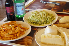 A meal for two: penne all'arrabbiata, linguine al pesto, cheese plate, red wine, sparkling water, and bread.